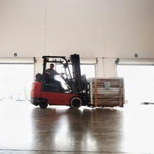 Forklift Driver Working In Warehouse