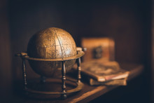 Vintage Globe Made Of Copper, In The Background A Chest And Books