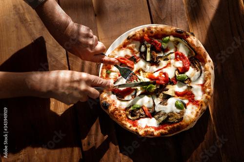Mani tagliano una fetta di pizza al gusto ortolana  isolata sopra un tavolo in Canvas Print
