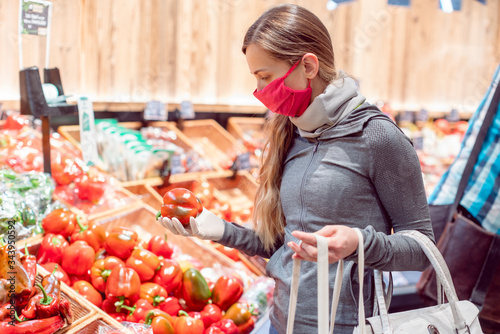 Woman with face mask shopping vegetables in supermarket