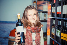 Close Up Of Cut Woman Holding And Showing A Bottle Of Red Wine