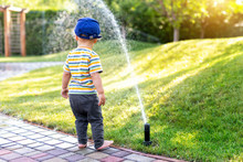 Cute Adorable Caucasian Blond Barefeet Toddler Boy In Cap Walking At Home Backyard Near Sprinkler Automatic Watering System Lawn In Garden. Child Little Helper Playing Gardening At Summer Outdoors