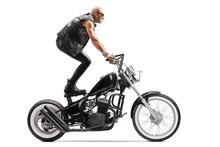 Crazy Daredevil Biker Riding A Chopper And Standing On The Seat