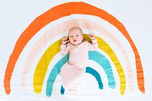 A Newborn Baby Girl Lying On A Rainbow Painted Blanket