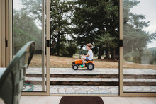 Boy Playing With Toy Tractor Outside House Seen Through Door