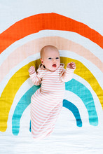 View From Above Of A Newborn Baby Lying On A Rainbow Painted Blanket