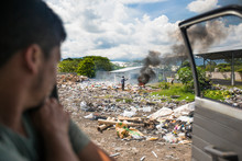 View From Vehicle Of Worker At Dump Burning Garbage.