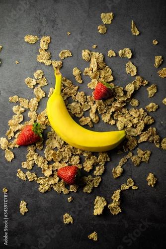 Vászonkép una banana, 3 fragole, cereali tutto attorno, su sfondo scuro