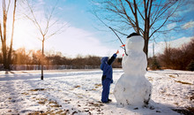 Boy Pointing At Snowman Outdoors