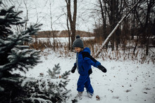 Little Boy In Snowsuit Playing...
