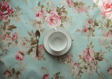 Cup Of Tea And Spoon On A Flowered Background