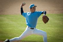 Pitcher In Light Blue And White Jersey During Wind Up On The Mound