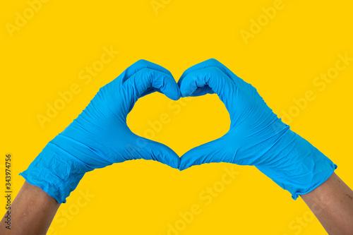 Valokuvatapetti Human wearing blue gloves rising hands making finger heart shape, disposable rub