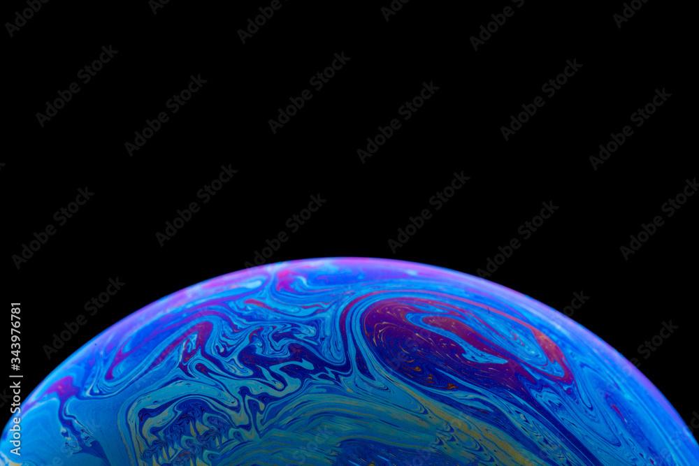 Fototapeta Burbuja de jabón simulando la atmosfera de un planeta con diferentes formas, colores y el fondo negro