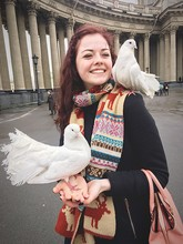 Young Woman With Fantail Pigeons Perching On Her Hands While Standing Against Kazan Cathedral
