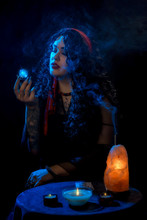 Girl Gypsy Fortune Teller With A Red Handkerchief At The Table With Nasty Cards Candles Against A Dark Background And Blue Lights