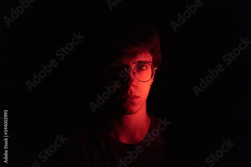 Fotomural Hombre joven en el medio de la oscuridad con la mitad de la cara iluminada por u