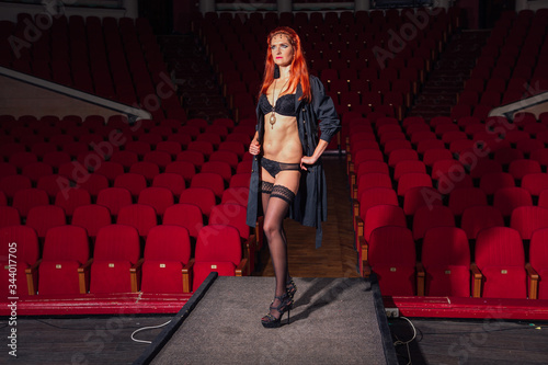 Full length portrait of a woman in black underware and a coat standing on theatr Wallpaper Mural