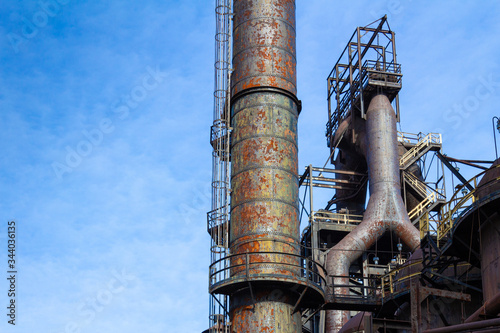 Photo Labyrinth of rusted metal structures, old abandoned steel mill, ample blue sky c