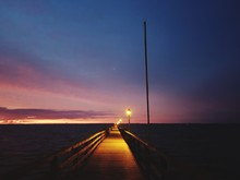 Pier Over Sea Against Sky At Sunset