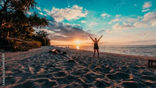 Fototapeta Beautiful shot of a cheerful female standing on the beach during the sunset obraz na płótnie