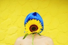 Woman Covered With Sunflower Against Yellow Background