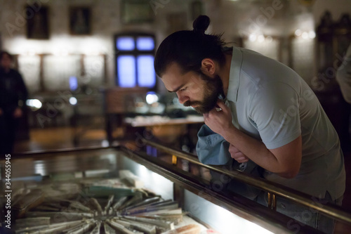 Stampa su Tela Attentive adult man exploring artworks in glass case in museum