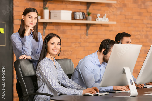 Professional technical support agent teaching young people in office Wallpaper Mural