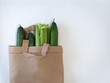 green vegetables in a reusable bag on a white background