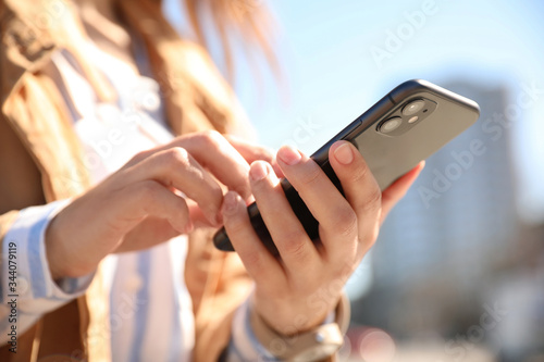 Fototapeta MYKOLAIV, UKRAINE - MARCH 16, 2020: Woman holding iPhone 11 Black outdoors, clos