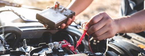 Fotografie, Obraz Mechanic repairman checking engine automotive in auto repair service and using d