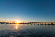 Silhouette Bridge Over River Against Clear Sky During Sunset