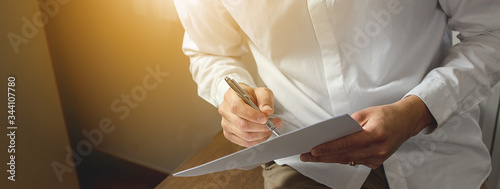 Fototapeta Close-up of businessman hands, sitting on wooden desk holding pen and papers. obraz