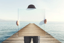 Man Holding Surreal Painting Of A Boardwalk