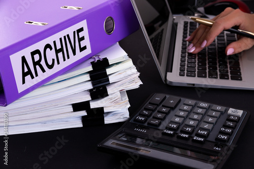 Text, word ARCHIVE is written on a folder lying on documents on an office desk with a laptop and a calculator Canvas Print