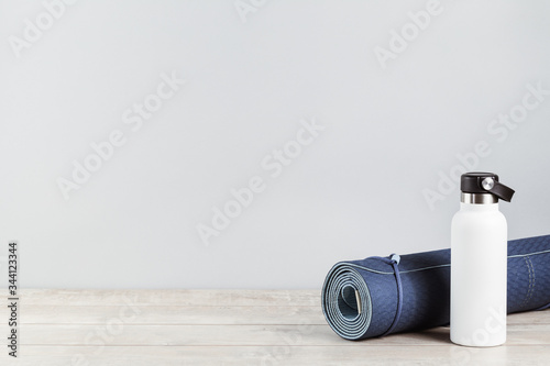 Fotografija Rolled blue yoga mat and white metal water bottle flask on grey wooden surface