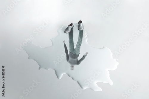 man reflection on a puddle; absence surreal concept Wallpaper Mural
