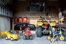 Inside View Open Door ATV Quad Bike Motorcycle Parking Messy Garage,clutter Stuff, Children Toys And Bicylce Storage Interior At Home. House Warehouse For Tools And Equipment . Garage Sale Facede