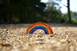Fototapeta Tęcza - Kids arts and crafts rainbow on a gravel path. NHS rainbow tribute created by children during the COVID-19 pandemic