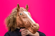 Leinwanddruck Bild - Portrait of blonde curly girl holding toy of horse's head on bright pink background. Trend photo without face in minimal style.