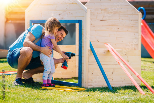 Obraz na plátne Dad and daughter making assembling wooden playhouse at home backyard garden