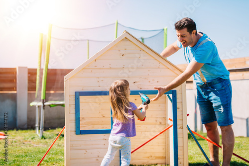 Fotografia, Obraz Dad and daughter making assembling wooden playhouse at home in backyard garden