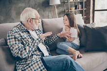 Photo Of Funny Two People Old Grandpa Little Granddaughter Sitting Comfort Sofa Telling Good Story Stay House Quarantine Safety Modern Design Interior Living Room Indoors