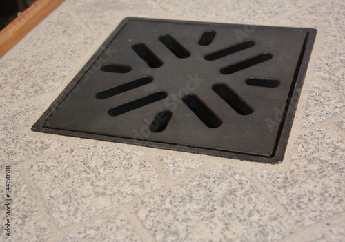 Fototapeta A close-up on yard drainage with metal sump pump cover in a paver cobble stone patio for water control