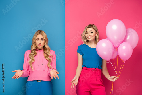 Smiling blonde girl holding balloons near offended sister on blue and pink background