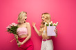 Leinwandbild Motiv Happy and shocked blonde women looking at each other while holding bouquets on pink background