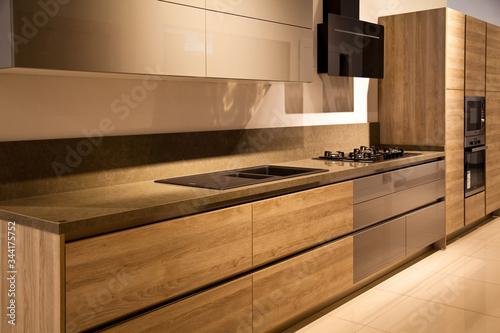 Fototapeta Interior of modern kitchen equipment, grey and oak cabinets obraz