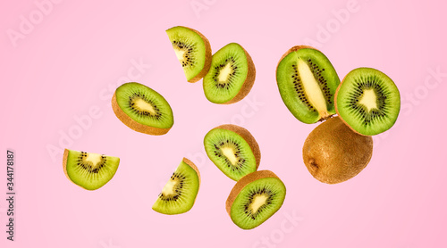 Obraz na plátně Fresh kiwi fruit flying in air on pink