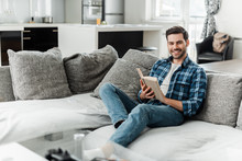 Selective Focus Of Handsome Man Smiling At Camera While Reading Book On Couch At Home