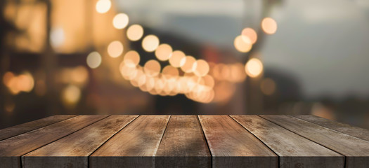 Wooden top table with bokeh light effect and blur restaurant on background